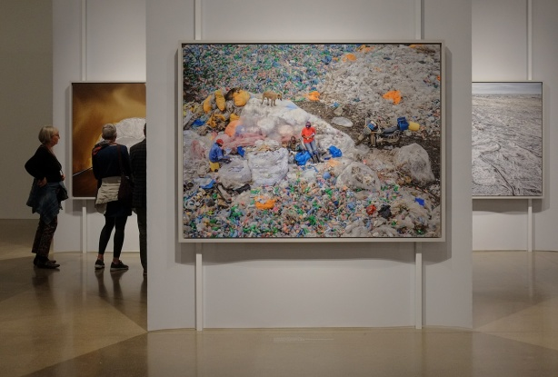 in an art gallery, a large photo of people and a dog among a large garbage dump