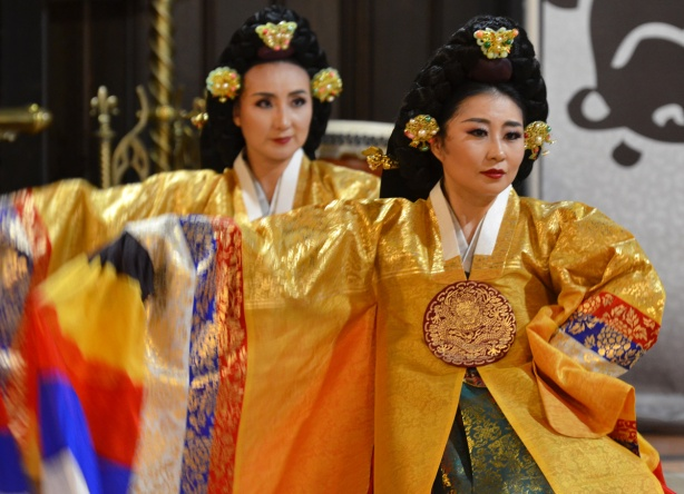 two Korean women in traditional costume, gold dresses, and decorated hair