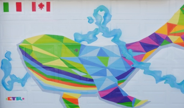 large mural of a many coloured whale swimming on a white garage door in an alley