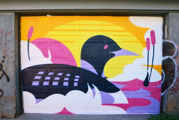 mural on a garage door of a loon swimming into the sunset