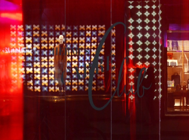 reflections in a window that has been lit with a red light, a mannequin is reflected from the store across the street