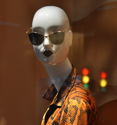 bald white mannequin with dark sunglasses and very dark red lipstick, looking at the camera, wearing an orange and brown top with a collar, reflected red, ywllow, and green lights behind her.