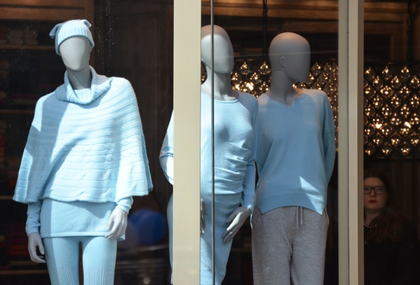 three grey femail mannequins dressed in pale blue in a store window