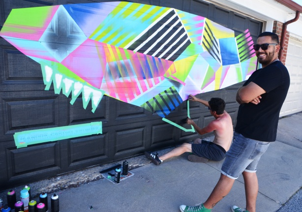 Andre Castro painting a mural of multicoloured whale on a garage door in a lane