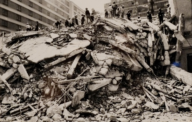 an old black and white photograph from the aftermath of the Mexico City earthquake of 1985, s pile of rubble with people standing on top of it.