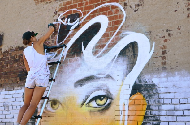 Anya painting a mural of a woman with wavy white and black hair, yellow face, yellow eyes, she's standing on a ladder