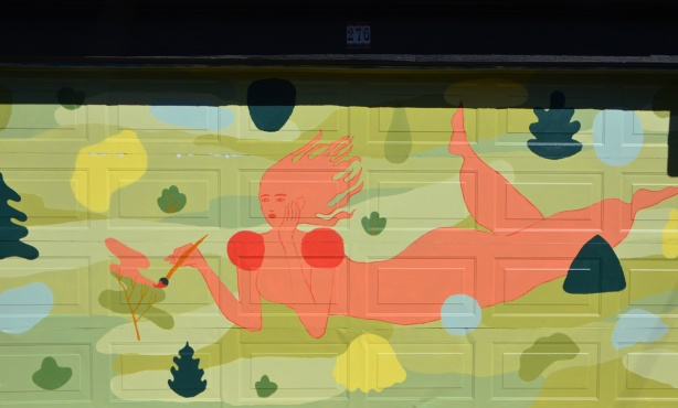 orange woman lying on the ground, holding a paint brush, mural on a garage door