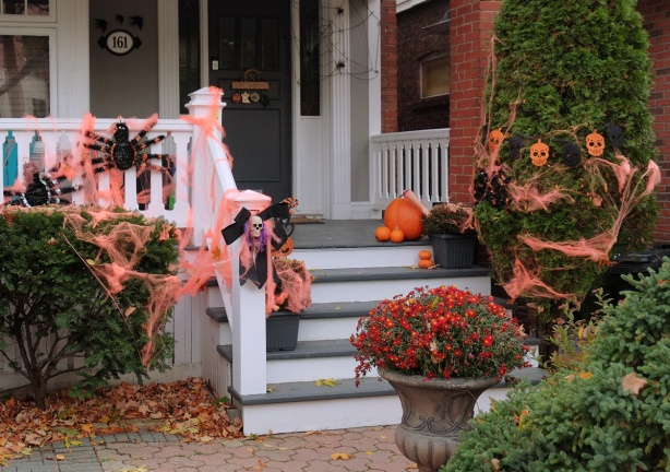 railing on front porch with orange webbing and large fuzzy black spiders, also orange skulls in the bushes beside the porch