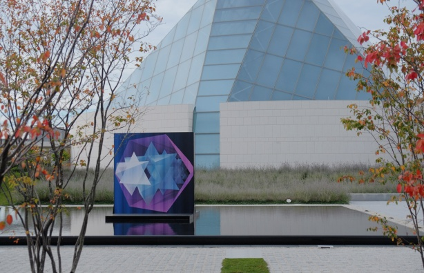 A painting in blue, pink, and purple, of stars, by Jacid Jah, in a reflecting pool with the Ismaili Centre behind it