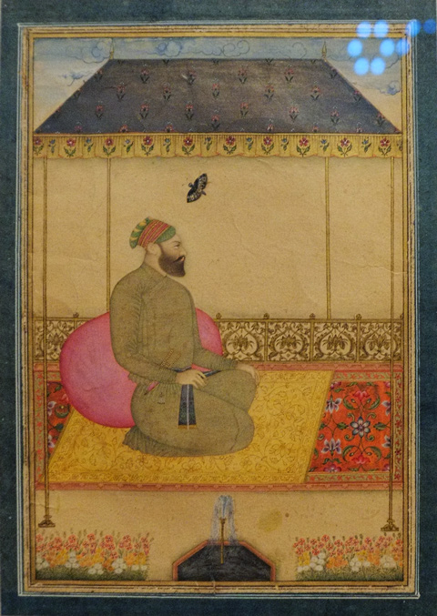 on display at the Aga Khan Museum, a painting, portrait of Nawab Bairam Khan, painted around 1710 to 1840, watercolour and gold on paper, scene is a man sitting on a carpet, under a tent roof, leaning on a large pink pillow