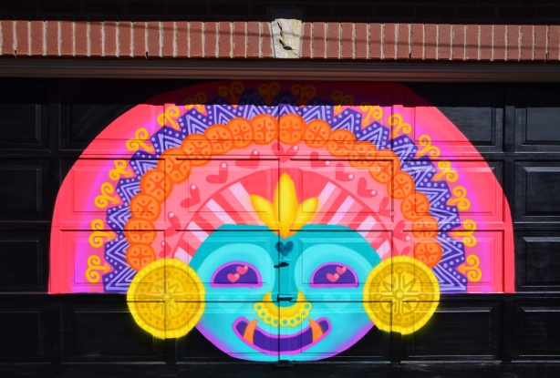 mural by muisca on garage door, bright colours, aztec face and head dress