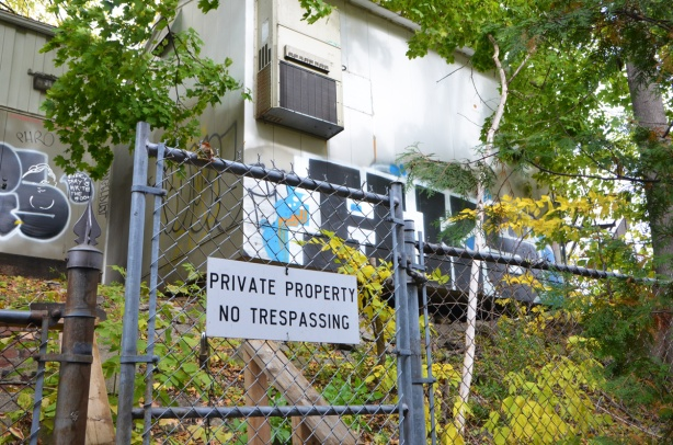 private property no trespassing sign on chainlink fence, trees and building behind, graffiti on the building