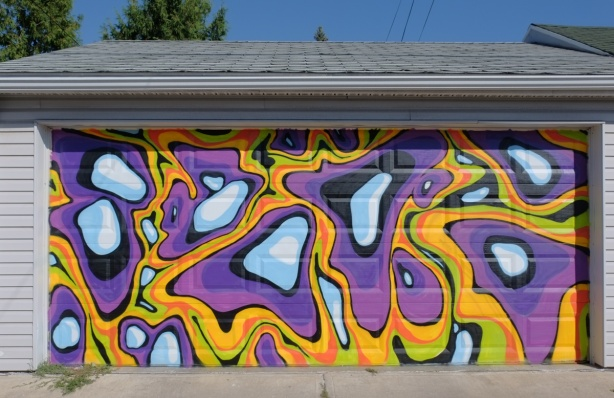 mural on a garage door of white, orange, and purple blobs and squiggles