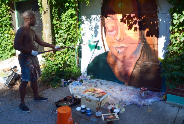 using a long handled brush to paint a mural of a woman's face on a garage door
