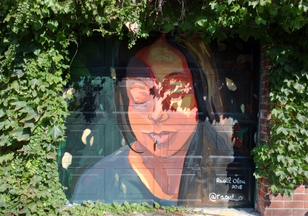 finished mural of a woman's face, with her eyes closed