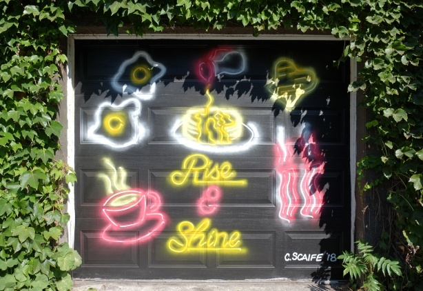 rise and shine mural by C. Scaife, looks like neon signs that would be in a restaurant, eggs cooking, hot coffee, bacon and the words rise and shine in cursive writing