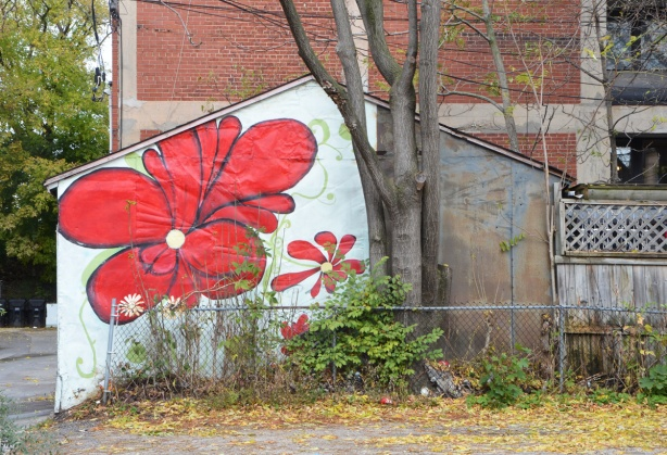 side of a garage painted with a couple of large red flowers