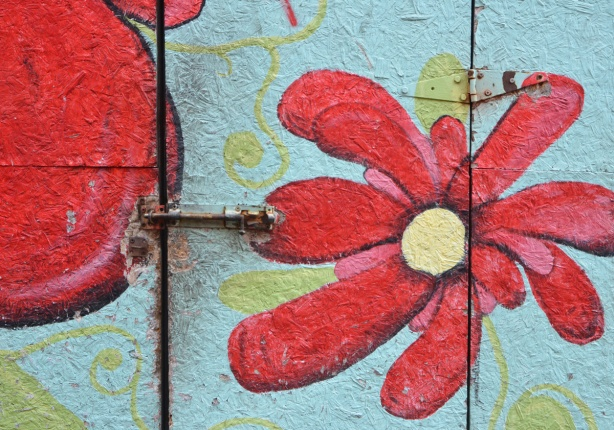 particle board door on a shed, painted pale blue and with a large red flower