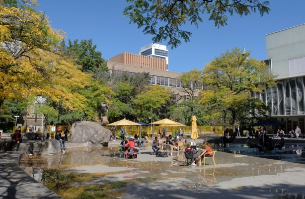 the pond outside Ryerson Image Centre is almost dry, there are tables, chairs and yellow umbrellas set up in the pond area, students sitting there.