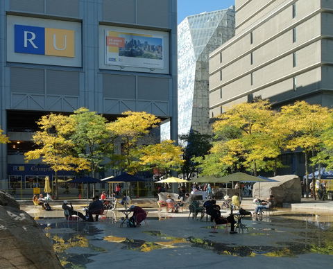 the pond outside Ryerson Image Cetnre is almost dry, there are tables, chairs and yellow umbrellas set up in the pond area, students sitting there. aas seen from inside the Image Center