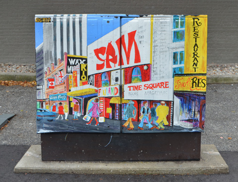 painted metal Bell box on sidewalk, painted with an old scene from Yonge street with signs for stores and restaurants