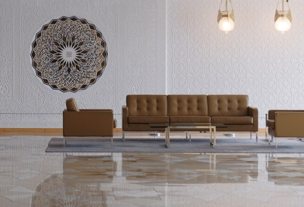 chairs and sofa in a large room, on grey carpet, most of floor is polished stone, medallion of stone on the white wall.
