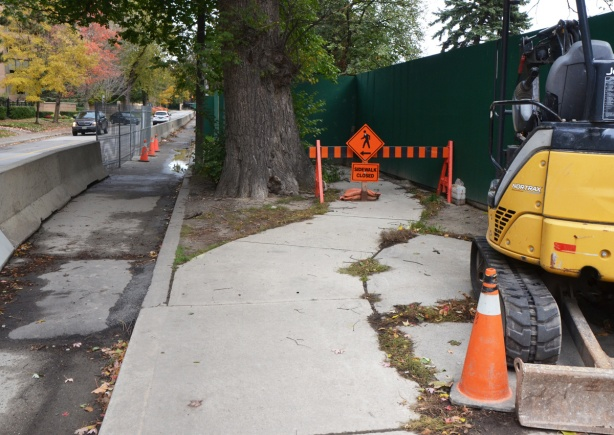 a small construction vehicle parked beside a sidewalk with orange barricade and sign that says pedestrians use other sidewalk, a path has been made on the side of the street for pedestrians.