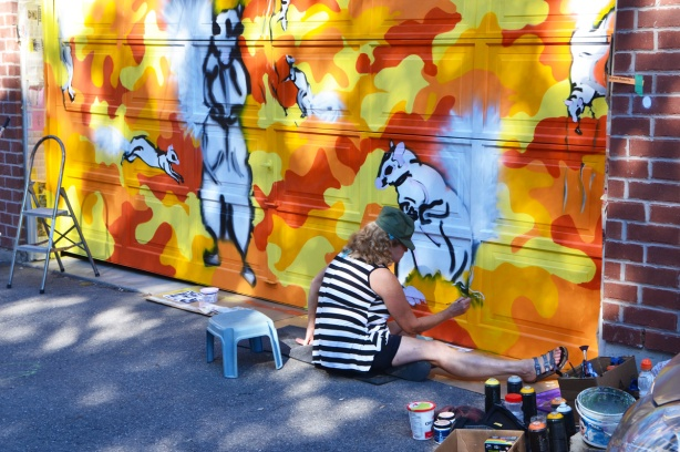 artist sitting on the ground while painting a mural on a garage door in a lane