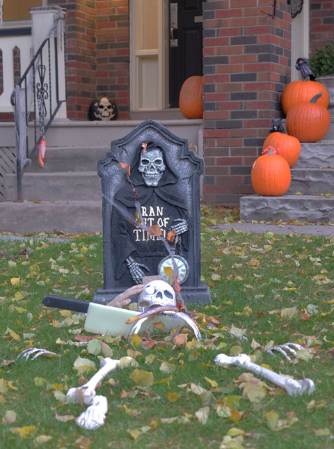skeleton and tombstone in the front yard of a house, porch has pumpkins on it