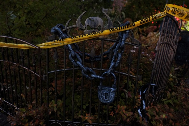 small fence with skull, lock and chain, and yellow caution tape in the front of house just before Halloweeen