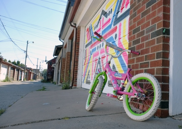 a pink kids' bike parked beside a garage door with a mural, no seat on the bike