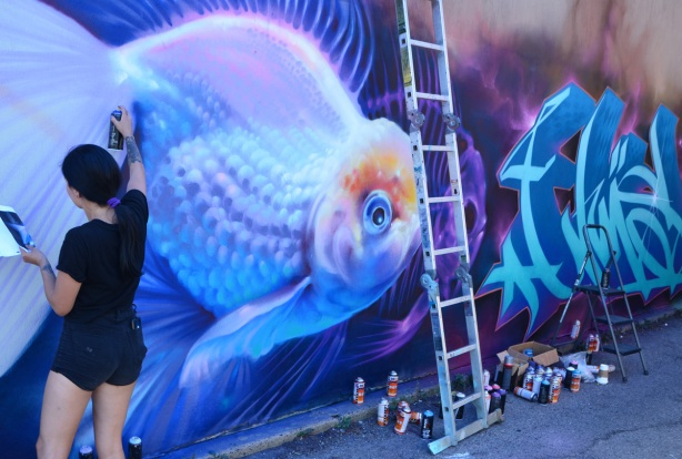 spray painting a mural of a fish swimming in the water