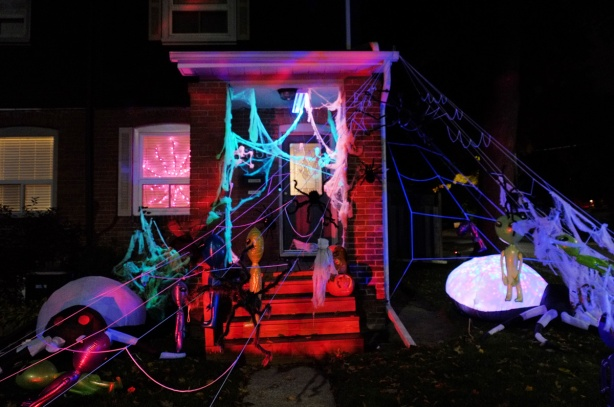 front porch and front yard of a house decorated with halloween, web, spiders, aliens, red lights, blue lights,