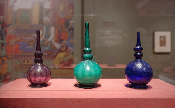 on display at the Aga Khan Museum, 3 glass bottles, rounded bottoms and narrow tops, one is marroon, one is teal and the last is royal blue