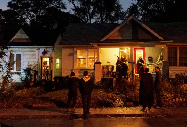 three small houses, each with front porches lit up and yards decorated for Halloween, Halloween night and trick or treaters are out with their parents