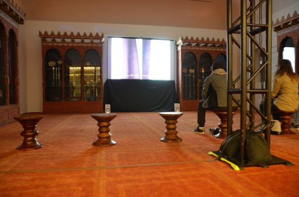 a room in the Aga Khan that is showing a video made in Tehran, two people are sitting on stools as they watch it, orange carpet on the floor, old decorated bookcases against the walls.