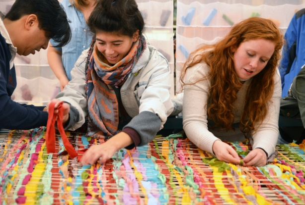 three people are taking their turn weaving coloured strips of fabric into a community weaving project