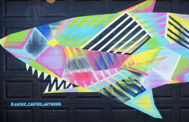 finished mural of a multicoloured whale on black background