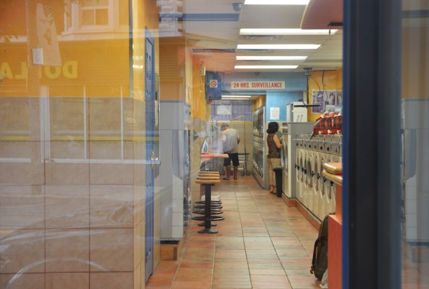 looking in a laundromat window, people, washing machines,
