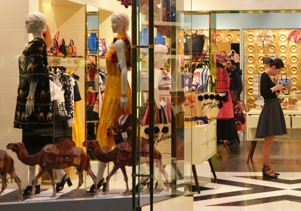 looking in the window and doorway of a womens clothing store in the Eaton Centre, mannequins in the window, saleswoman in the door,