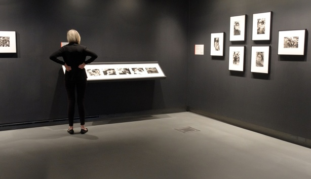 woman dressed in black in a gallerywith black walls,looking at black and white photos on the wall
