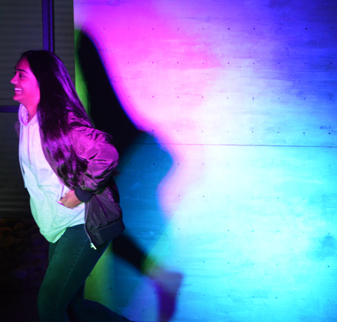 woman runs past a white screen that is being lit with coloured lights, making her shadow coloured