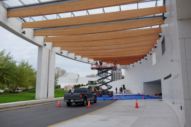 a pick up truck and a lift in front of the entrance to the Ismaili Centre, workmen are re-staining the large wood beams that support the glass roof.