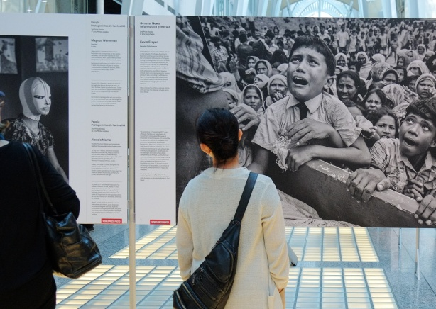 a woman stands in front of a photo of a crowd of people, with a boy in the front of the crowd who is crying