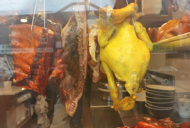 looking in a restaurant window, meat hanging in a windiw including a rather yellow chicken, some ribs,