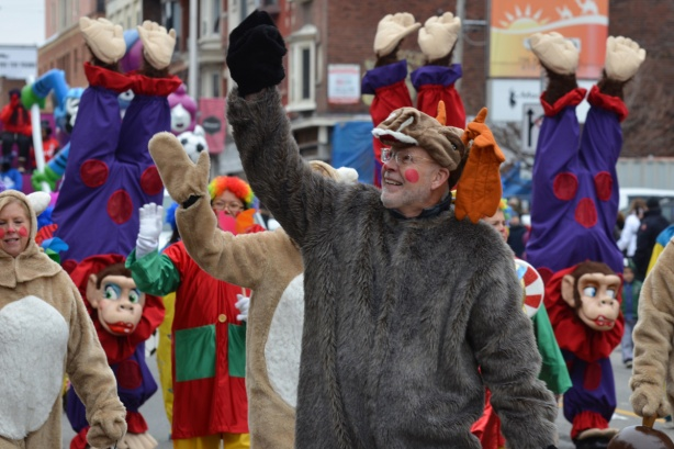 a man in a fuzzy grey animal costume waves to the crowd on the sidewalk at the Santa Claus parade