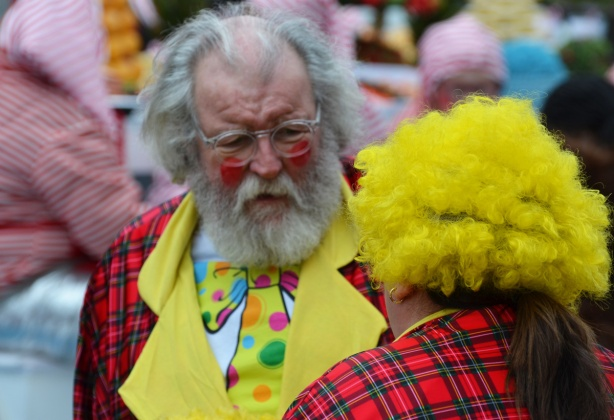older man with grey hair, beard & moustache, and slightly balding, talks to another clown in a bright yellow wig