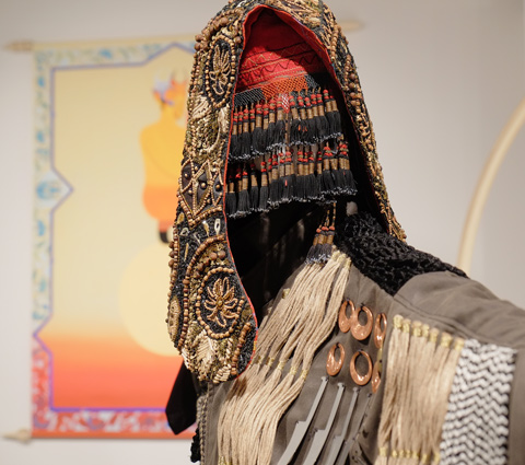 part of a life sized sculpture, or installation, of a figure dressed in a beaded hood and mask