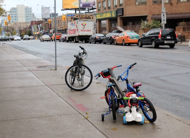 an adult bike locked to a ring, two kids bikes and a toddlers push car locked to a second ring, on a sidewalk on Dundas West, cars and buildings in the background.
