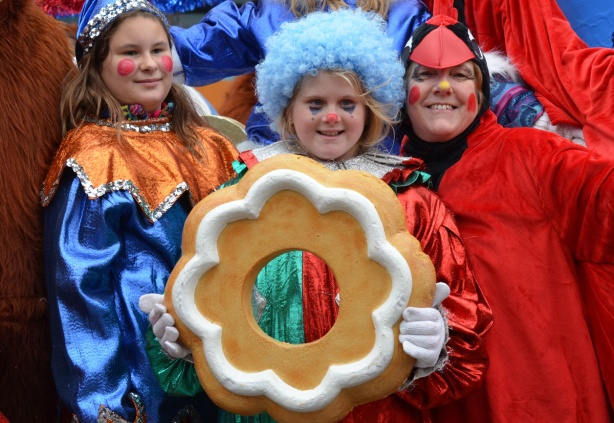 three people involved with the Santa Claus parade pose for a picture. A woman in a red cardinal costume, a girl with a light blue wig holding an oversized gingerbread cookie with white icing, and another girl in a shiny blue and orange outfit